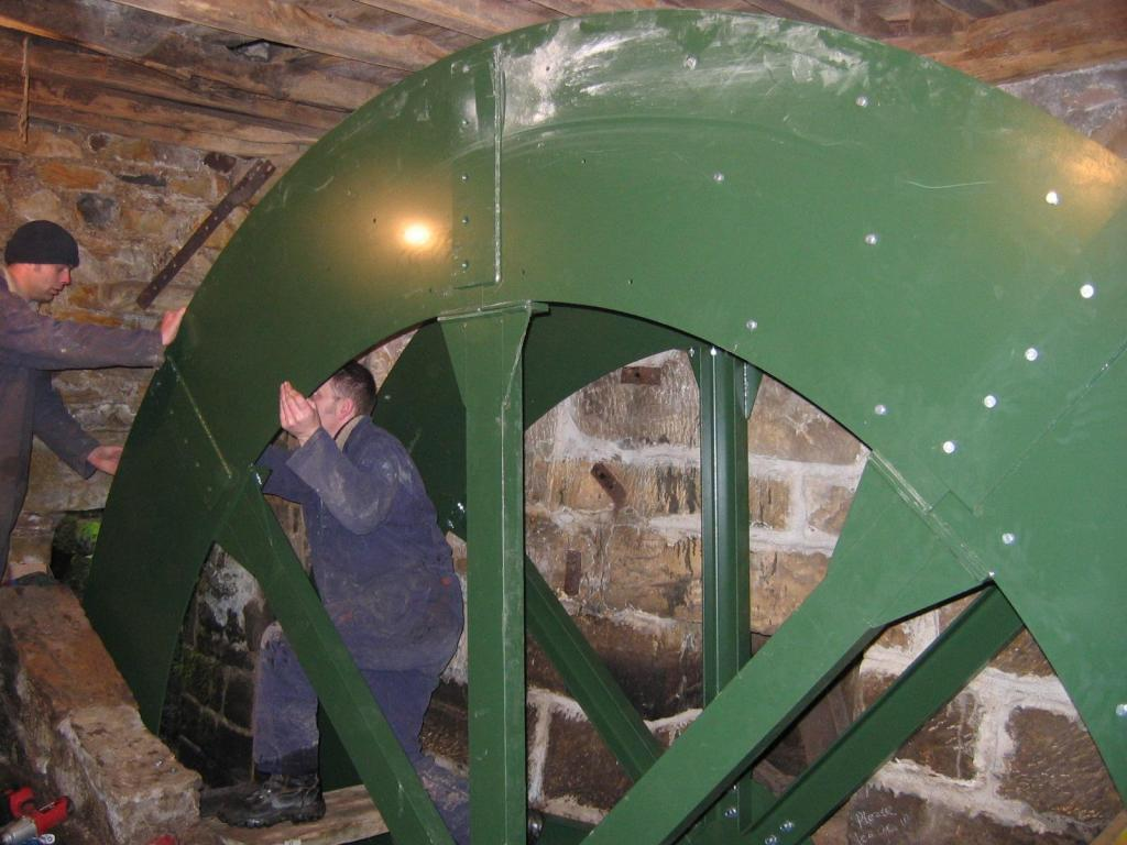 Installing the waterwheel ~ Photo Credit: Mannpower Consulting Ltd